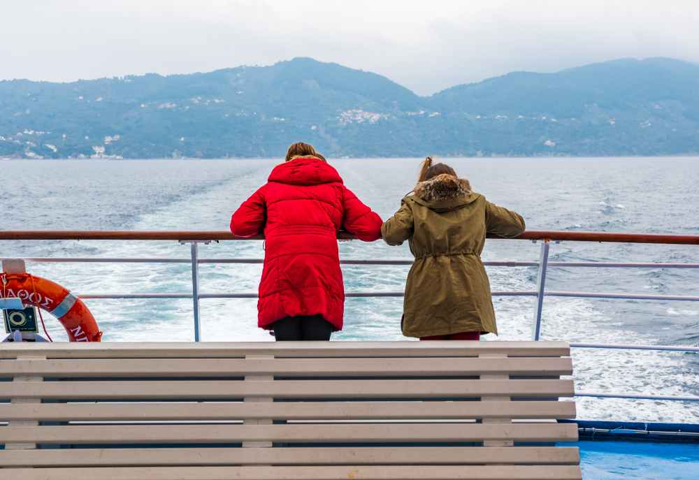 greece - Beautiful winter scenery with adorable young girls enjoying ferry ride staring at the deep blue aegean sea. Children having fun on family vacation in Greece. Kids sailing on a boat.