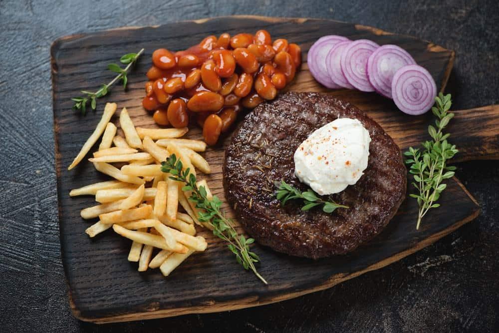 Serbia - Novi Sad - Grilled serbian pljeskavica with kajmak cheese, prebranac, fries and red onion on a rustic wooden serving board,