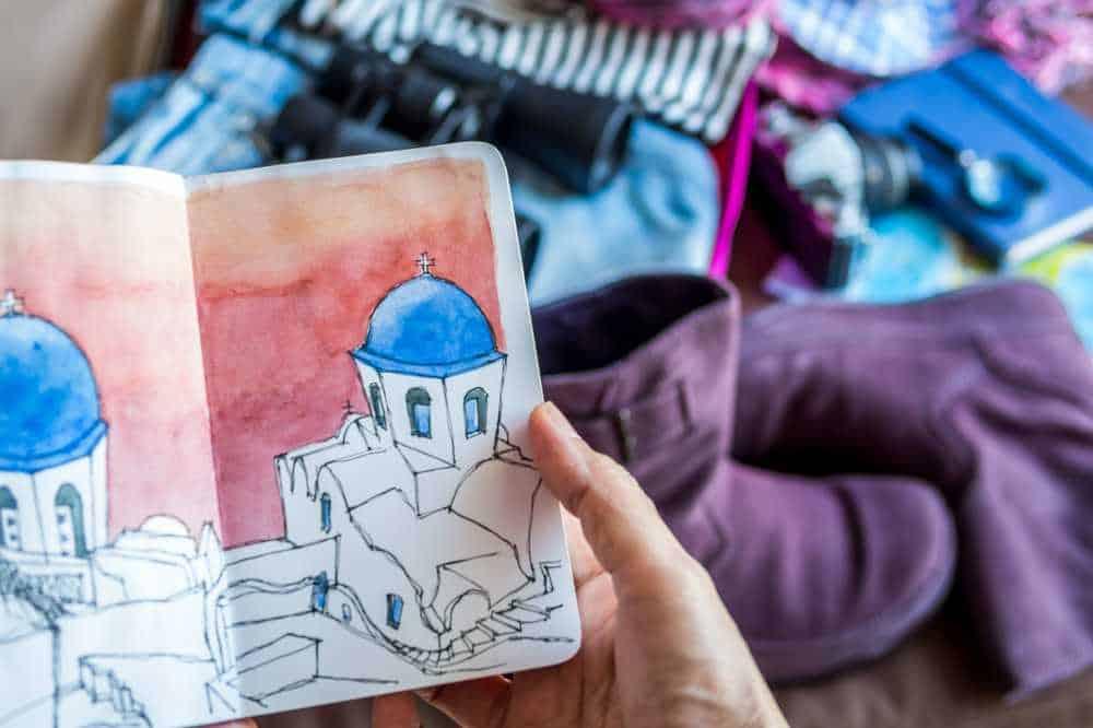 Greece - Santorini - Hand holding sketch book illustration over luggage stuff scattered background /traveling concept