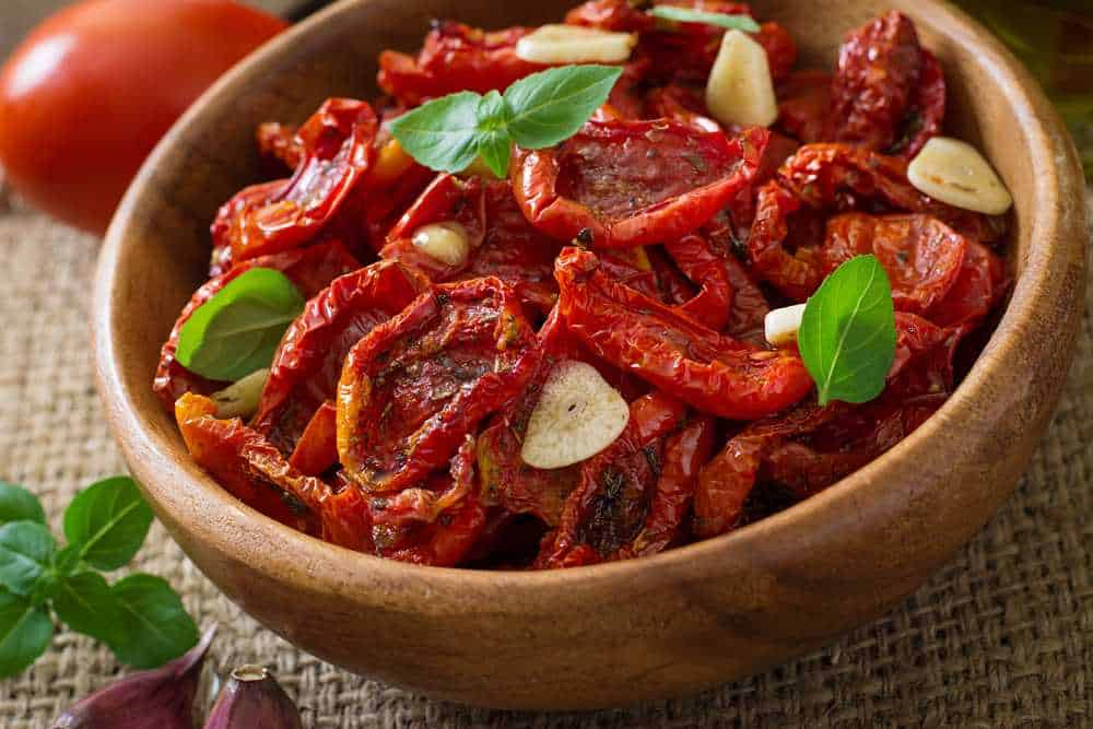 Greece - Santorini - Sun-dried tomatoes with herbs and garlic in wooden bowl