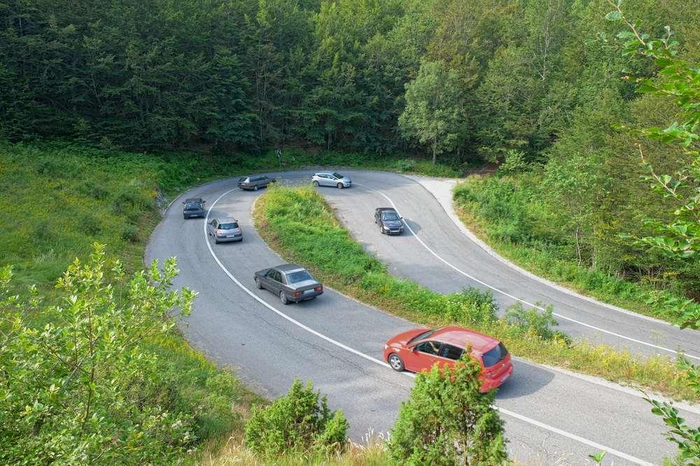 Montenegtro - cars on hairpin turn mountain road in Montenegro