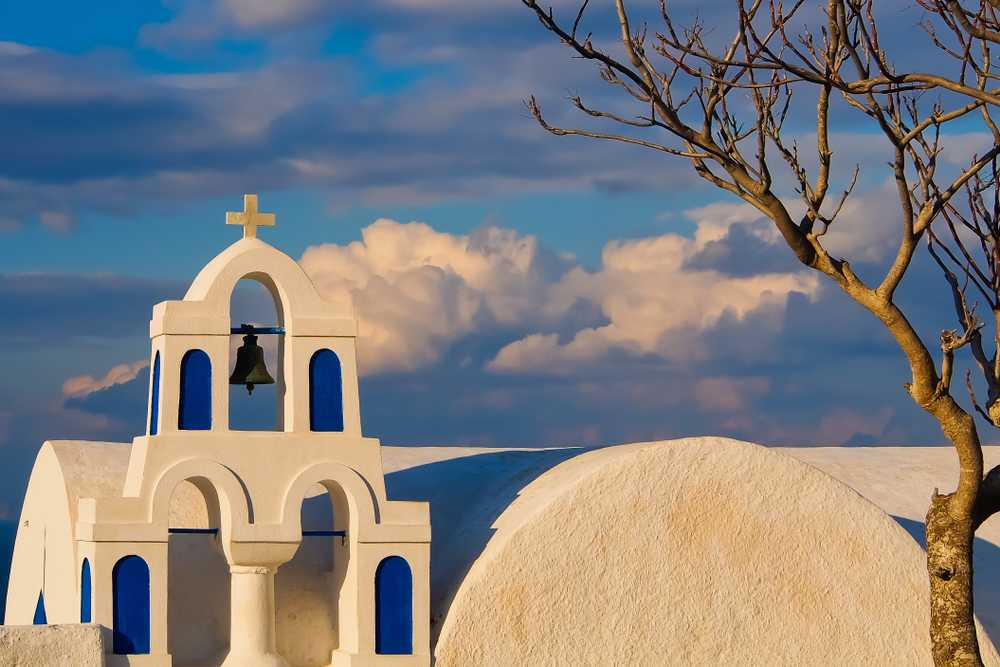 Greece - Santorini - close up view of church bells with bare tree in the foreground oia santorini greece