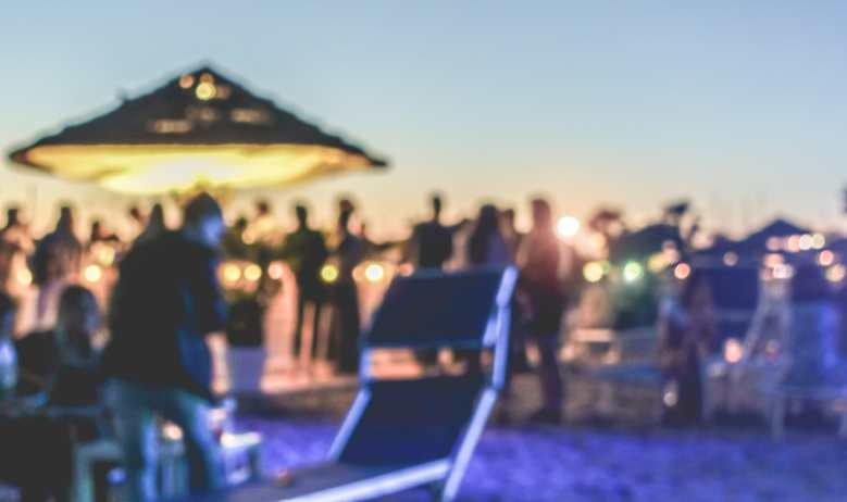 Serbia - Music Festival - Blurred people having sunset beach party in summer vacation - Defocused image - Concept of nightlife with cocktails and music entertainment