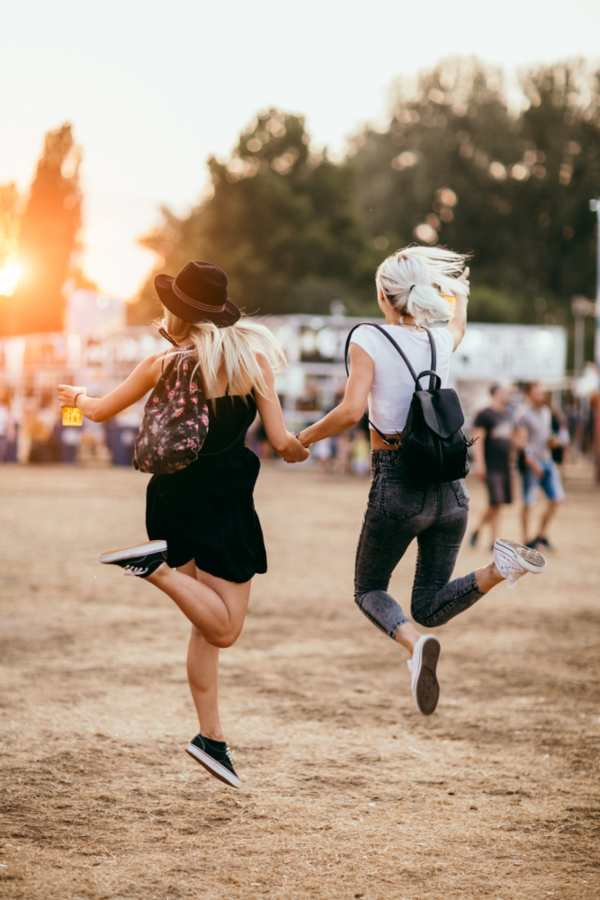 Serbia - Novi Sad - Two female friends jumping and having fun at music festival. Back view