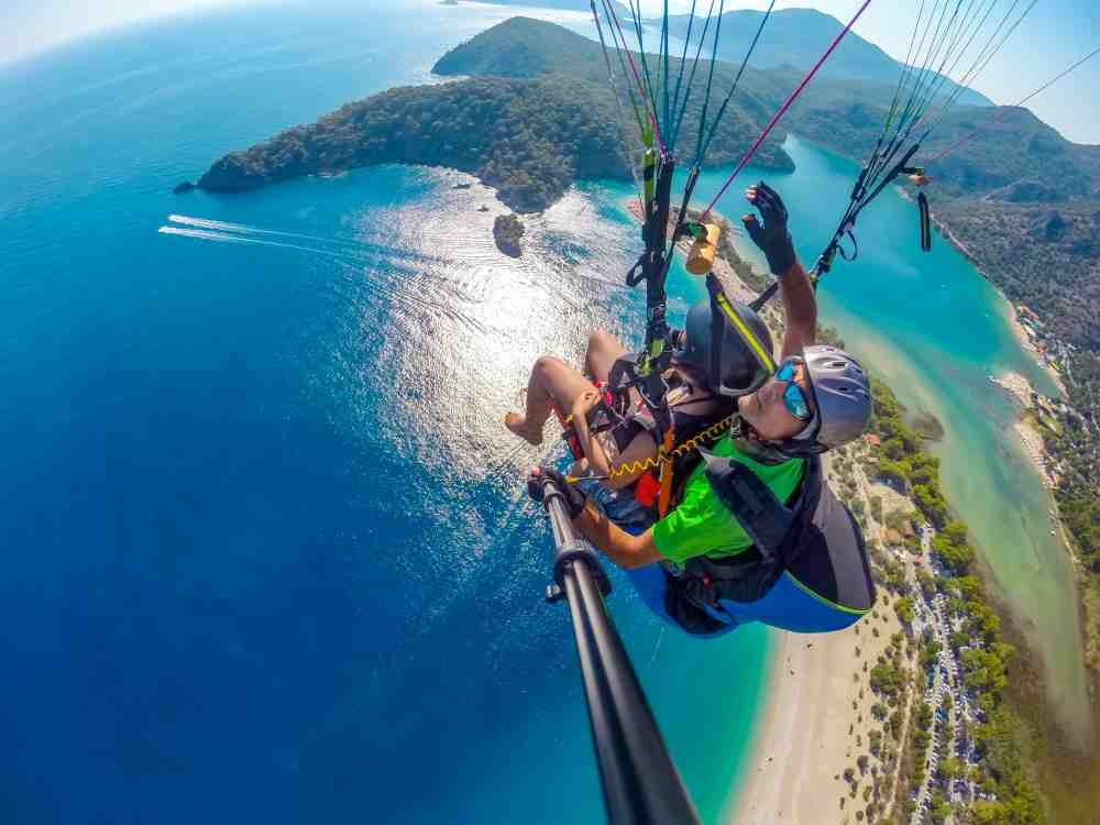 Turkey - Kas - Paragliding in the sky. Paraglider tandem flying over the sea with blue water and mountains in bright sunny day. Aerial view of paraglider and Blue Lagoon in Oludeniz, Turkey. Extreme sport. Landscape