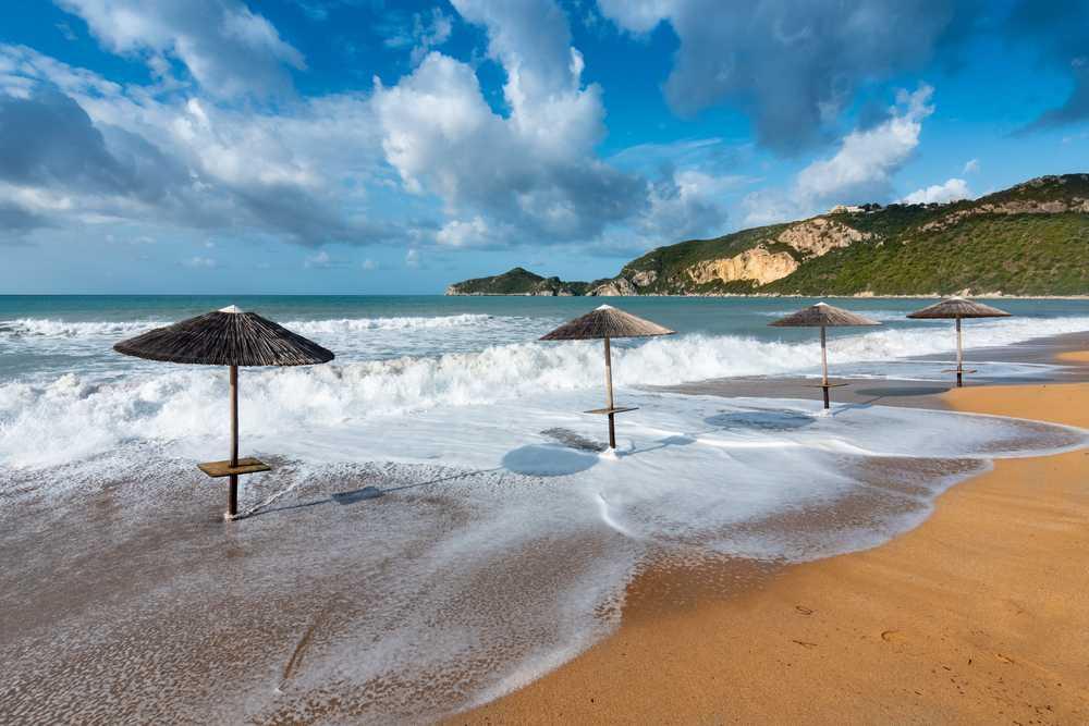 Greece- Corfu - Four sun umbrellas on a golden beach (Saint George, Corfu)
