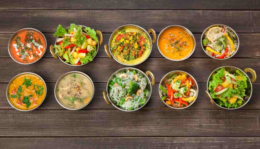 romania cluj napoca - Vegan or vegetarian restaurant dishes top view, hot spicy indian soups, rice and salads in copper bowls. Traditional indian cuisine meal assortment on wood background. Healthy eastern local food