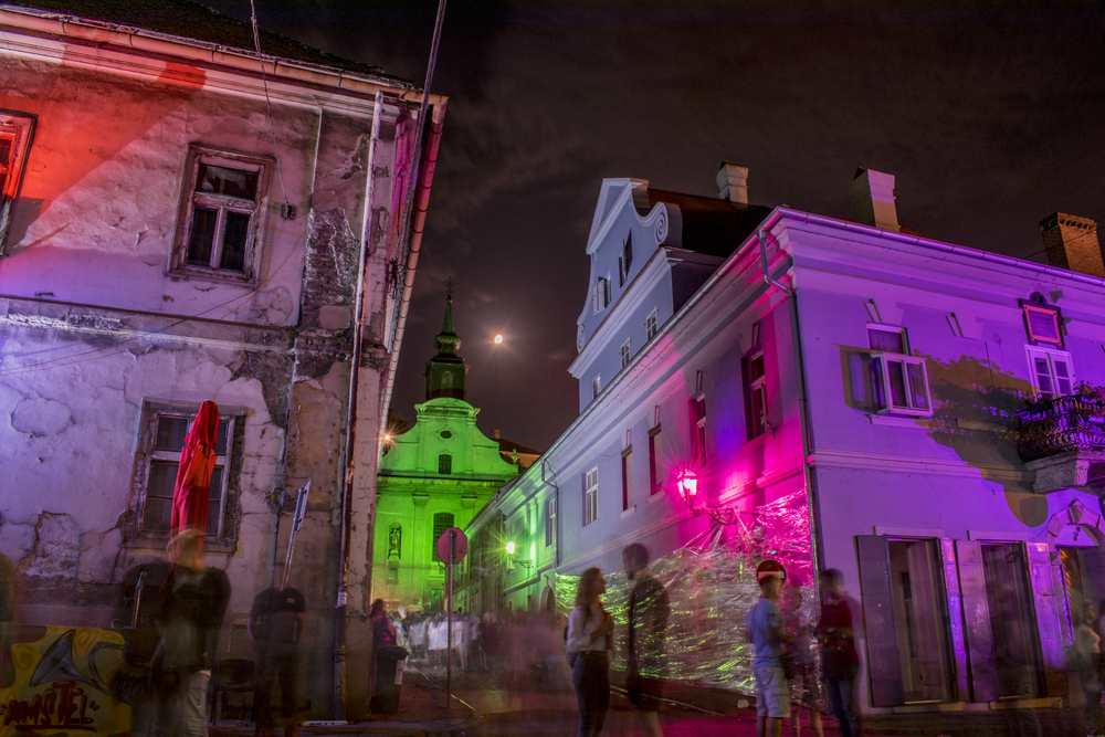 people passing by on music festival on the streets of Petrovaradin beneath fortress
